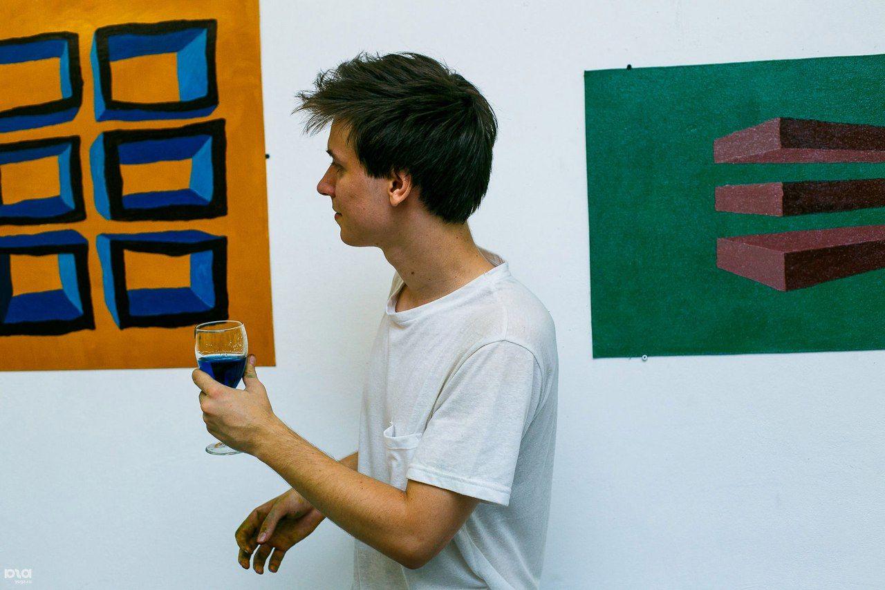 Художник Максим Алехин с бокалом синей жидкости в руке ©Фото Дениса Яковлева, Юга.ру