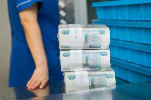 Работники кассового подразделения проверяют целостность упаковки и укладывают банкноты в кассеты ©Фото Елены Синеок, Юга.ру