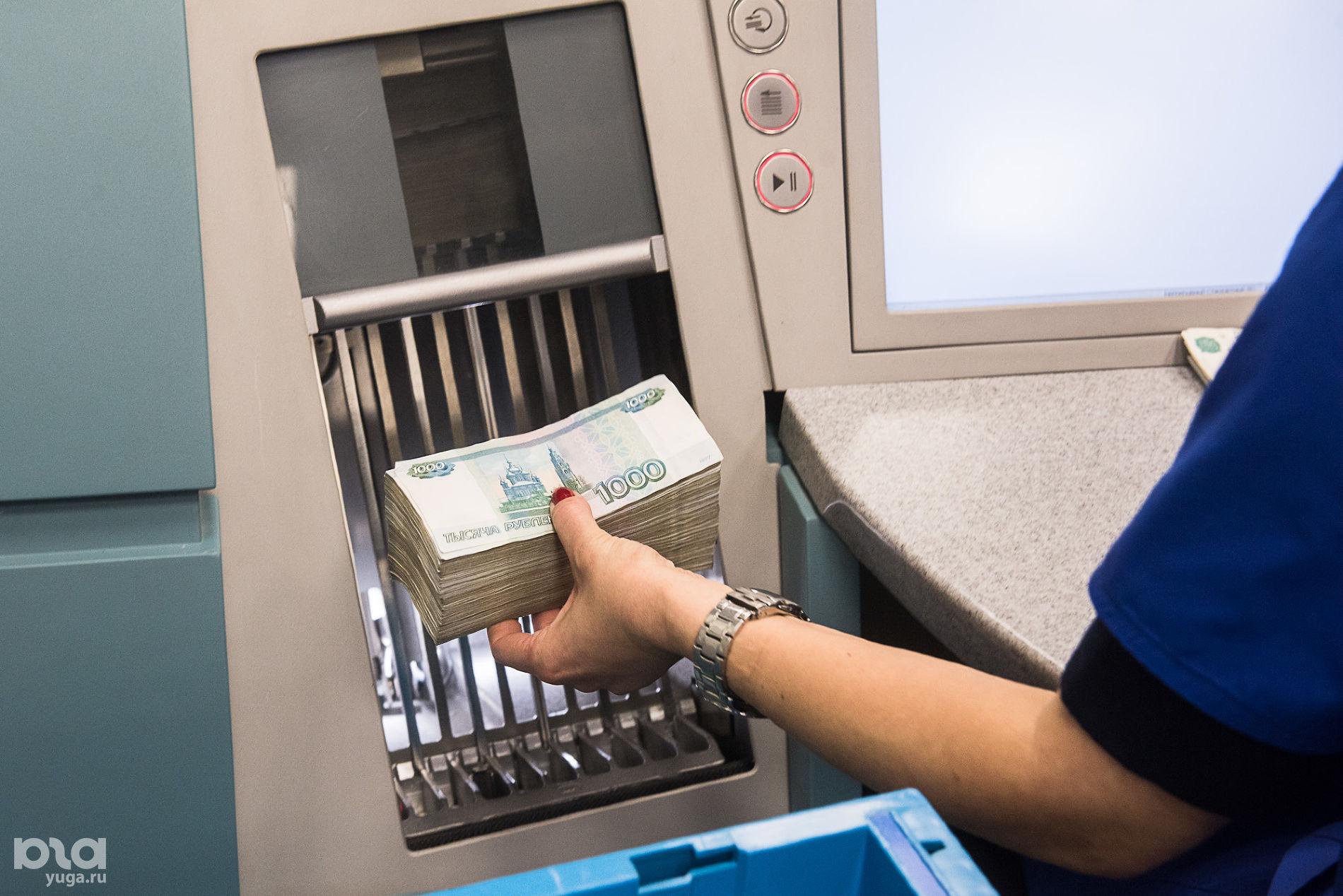 Оператор загружает банкноты в счетно-сортировальную машину ©Фото Елены Синеок, Юга.ру