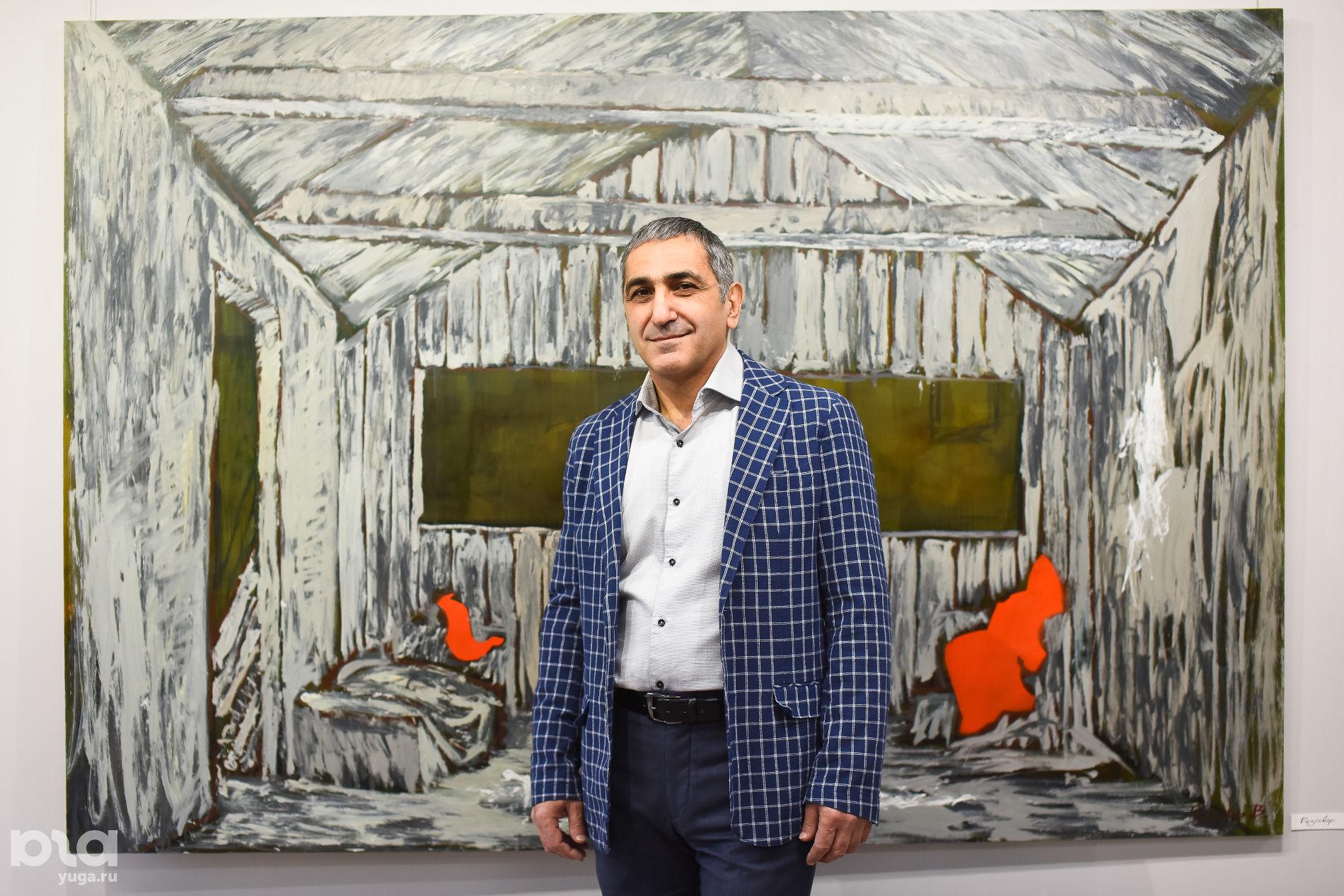 Владелец галереи «Доротея» Артур Григорян на фоне картины Владимира Кухаря «Разговор» ©Фото Елены Синеок, Юга.ру