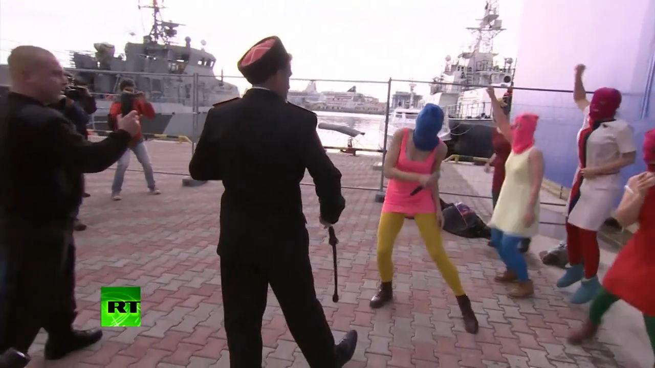 Люди в казачьей форме прерывают выступление ВИА Pussy Riot ©Кадр из видео канала «Russia Today», youtube.com/rtrussian
